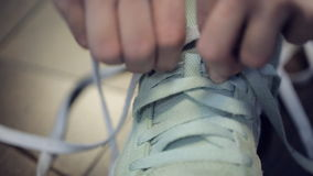 Human Hands hastily knotted bright light long laces on sneakers. stock video