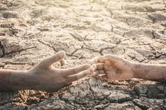 Human hands helping on cracked dry ground royalty free stock photography