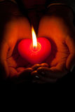 Human hands hold heart shaped burning candle. Against dark background Royalty Free Stock Photos