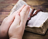 Human hands holding the Bible and praying Stock Photo