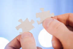 Human hands holding details of puzzle Stock Image