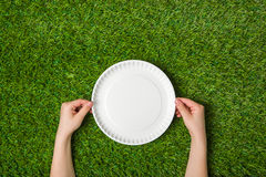 Human hands holding empty paper plate on grass Royalty Free Stock Photo