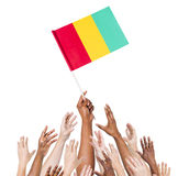 Human Hands Holding The Flag Of Guinea Royalty Free Stock Images