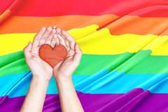Human hands holding heart. With rainbow flag background. LGBT concept royalty free stock photo