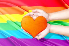 Human hands holding heart. With rainbow flag background. LGBT concept stock image