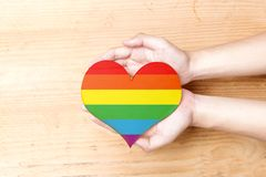Human hands holding heart with rainbow flag. Over wooden table background. LGBT concept stock image