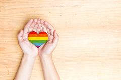 Human hands holding heart with rainbow flag. Over wooden table background. LGBT concept royalty free stock photography