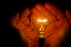 Human hands holding a light bulb to conserve energy darkness Stock Image