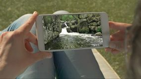 Human hands holding a mobile with water cascade video. Slow motion mountain river video stock footage