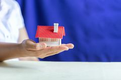 Human hands holding model of dream house. royalty free stock image