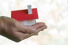 Human hands holding model of dream house. stock photography