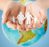 Human hands holding paper family over earth globe. People, population, charity and life concept - close up of human hands holding paper family over earth globe stock image