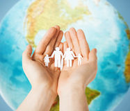 Human hands holding paper family over earth globe. People, population, charity and life concept - close up of human hands holding paper family over earth globe stock photography