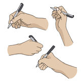 Human hands holding a pen and writing on paper Stock Images