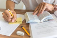 Human hands holding pencil writing into sticky notes. In the library royalty free stock image