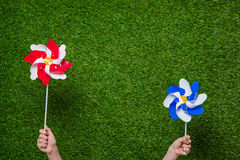 Human hands holding pinwheels over grass Royalty Free Stock Image