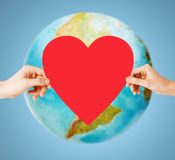 Human hands holding red heart over earth globe Royalty Free Stock Photography