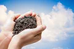 Human hands holding soil holds up the sky in the background.Environment Day concept. Ecology concept. Stock Photo