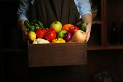 Human hands holding wooden box with different fruits. And vegetables closeup royalty free stock images