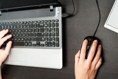 Human hands on a laptop computer keyboard. And and smartphone nearby royalty free stock photo