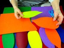 Human hands that make applique petals of colored felt. Stock Image