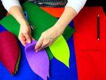 Human hands that make applique petals of colored felt. Royalty Free Stock Photo