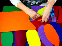 Human hands that make applique petals of colored felt. Stock Images