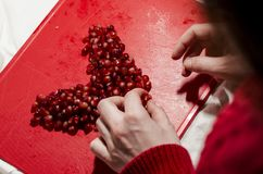 Hands making heart in front of pomegranate seeds on the red cutting board royalty free stock photo