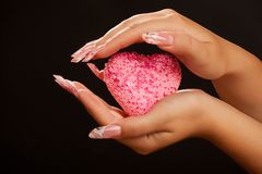 Human hands with manicure hold pink heart. Human hands with long acrylic fingernail and beautiful manicure holding pink heart. Over black royalty free stock photos
