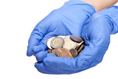 Human hands in medical gloves holding coins Royalty Free Stock Photo
