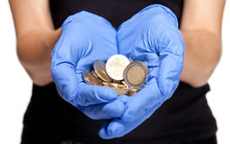 Human hands in medical gloves holding coins Stock Image