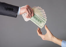 Human hands passing fan of dollar banknotes Royalty Free Stock Photo