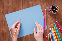 Human hands with pencil drawing something on the blue paper on wooden table Stock Photography