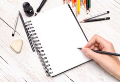 Human hands with pencil draws in notebook. Royalty Free Stock Photo