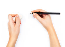 Human hands with pencil and erase rubber writting something on w Stock Photography