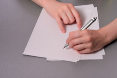 Human hands with pencil writing on paper and erase rubber on wooden table background stock photo