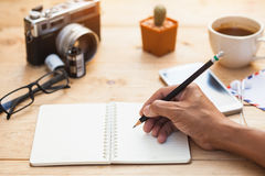 Human hands with pencil writing on paper on wooden table. And camera,coffee cup,glasses is background stock image