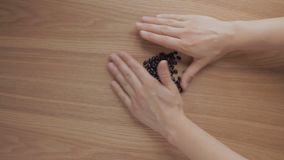 Human hands pile up black beans on wooden table stock footage