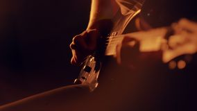 Human hands playing on electric guitar. Close up of rock musician playing guitar on stage with scenic illumination. Bassist playing electric bass guitar stock video