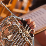 Human hands playing the French horn. French horn in the hands of a musician closeup Stock Photos