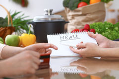 Human hands pointing into note book with copy space area. Two woman making menu in the kitchen, closeup. Cooking and. Friendship concept Stock Photos