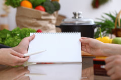 Human hands pointing into note book with copy space area. Two woman making menu in the kitchen, closeup. Cooking and. Friendship concept Stock Image