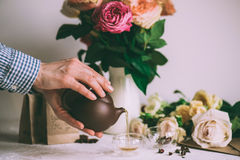 Human hands pouring Fresh herbal tea fron teapot to glass Royalty Free Stock Images