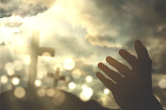 Human hands praying with cross symbol. Picture of human hands praying to the GOD with christian cross symbol and bright sunlight on the sky Royalty Free Stock Image