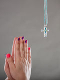 Human hands praying to god with cross necklace. Royalty Free Stock Images