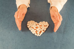 Human hands protect  guard a heart shape made from pills Royalty Free Stock Photography