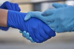 Human hands in protective gloves against covid-19 coronavirus pandemic, handshake in quarantine outdoors in city