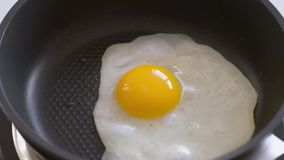 Egg fried on pan. Human hands puts egg on frying pan. Egg being dropped on hot pan. Broken Chicken egg falls into the frying pan. Cooking egg on fry pan. Top stock video footage
