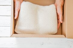 Human hands puts out the new just arrived with mail sweater on the white wooden table royalty free stock image