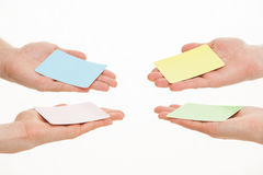 Human hands reaching out colorful paper cards. On white background